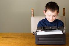 Écriture de petit garçon sur une vieille machine à écrire Photographie stock libre de droits