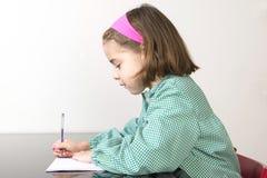 Écriture de petite fille dans un carnet Images stock
