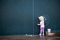 Écriture de petite fille sur le grand tableau noir Photo libre de droits