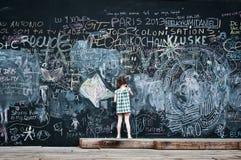 Écriture de petite fille sur le grand tableau noir Photographie stock libre de droits