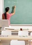 Écriture de professeur sur le panneau de craie dans la salle de classe Photo libre de droits
