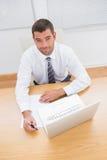 Écriture de sourire d'homme d'affaires à son bureau Photographie stock libre de droits