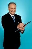 Écriture de sourire d'homme d'affaires sur la planchette Image libre de droits