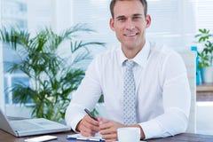 Écriture de sourire d'homme d'affaires sur le carnet Photo libre de droits