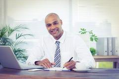 Écriture de sourire d'homme d'affaires sur un carnet Photos stock