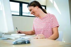 écriture de sourire de femme d'affaires dans un bloc-notes Photo libre de droits