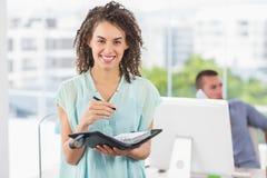 Écriture de sourire de femme d'affaires sur un carnet Photos libres de droits