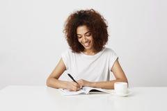 Écriture de sourire de fille africaine gaie dans le carnet sur le lieu de travail au-dessus du fond blanc Image stock