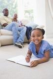 Écriture de sourire heureuse de petite fille de portrait sur le bloc-notes Image stock
