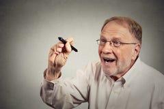 Écriture enthousiaste supérieure d'homme quelque chose avec le stylo sur le tableau noir Image stock