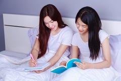 Écriture et lecture de deux femmes un livre sur le lit dans la chambre à coucher Photo libre de droits