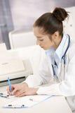 Écriture femelle de docteur au bureau images stock