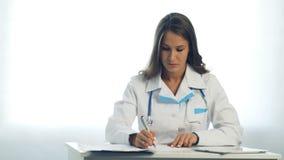 Écriture femelle de médecin quelque chose se reposant à son bureau clips vidéos