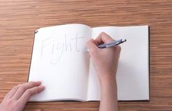 Écriture femelle de main dans le carnet sur la table Image stock