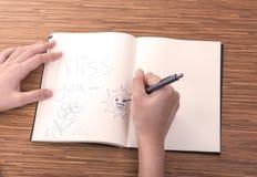 Écriture femelle de main dans le carnet sur la table Images stock