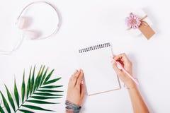 Écriture femelle de main dans un carnet avec le crayon rose Photos stock