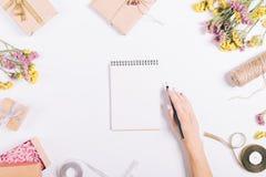 Écriture femelle de main dans un carnet de papier sur une table blanche avec le De Images stock