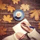 Écriture femelle de main quelque chose dans le carnet près de la tasse Image stock