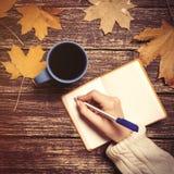 Écriture femelle de main quelque chose dans le carnet près de la tasse de café Images stock
