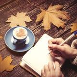 Écriture femelle de main quelque chose dans le carnet près de la tasse de café Photographie stock