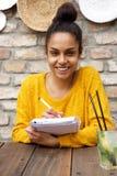 Écriture femelle de sourire sur le carnet photographie stock