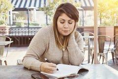 Écriture femelle hispanique en son journal dans un café extérieur images libres de droits
