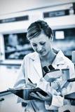 Écriture femelle sérieuse de scientifique sur son presse-papiers devant un microscope images libres de droits