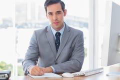 Écriture gaie d'homme d'affaires à son bureau Photo stock