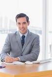 Écriture heureuse d'homme d'affaires à son bureau Photographie stock libre de droits