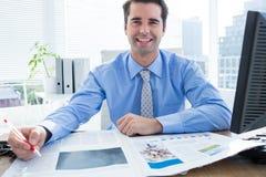 Écriture heureuse d'homme d'affaires à son bureau Photo stock