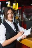 Écriture heureuse de barmaid en bloc-notes photographie stock libre de droits