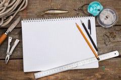 Écriture-livre avec des articles de pêche et des outils de conception sur la BO en bois Image stock