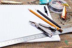 Écriture-livre avec des articles de pêche et des outils de conception sur le boa en bois Photo stock
