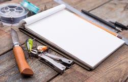 Écriture-livre avec des articles de pêche et des outils de conception sur le boa en bois Images stock