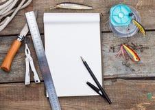 Écriture-livre avec des articles de pêche et des outils de conception sur le boa en bois Photographie stock libre de droits