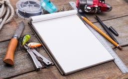 Écriture-livre avec des articles de pêche et des outils de conception sur le boa en bois Photographie stock