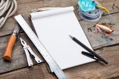 Écriture-livre avec des articles de pêche et des outils de conception sur le boa en bois Image stock