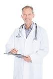 Écriture mâle de docteur sur la planchette Photos libres de droits