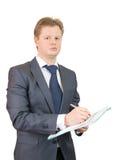 Écriture mâle de gestionnaire quelque chose sur un cahier photos stock