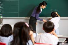 Écriture mâle de pupille sur le tableau noir à l'école chinoise photographie stock libre de droits