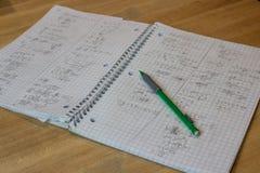 Écriture malpropre ouverte de carnet de maths avec le crayon Images stock