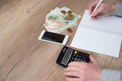 Écriture masculine de main dans un stylo-plume de journal intime d'affaires avec la calculatrice Image libre de droits
