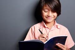 Écriture mignonne de petit garçon sur un livre Image stock