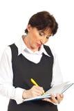 Écriture sérieuse exécutive de femme à l'ordre du jour Images stock