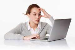 Écriture soucieuse de l'étudiante 20s sur l'ordinateur portable dans le bureau blanc Images libres de droits