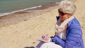 Écriture supérieure de femme au carnet sur la plage d'été clips vidéos