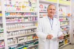 Écriture supérieure de sourire de pharmacien sur le presse-papiers Photo libre de droits
