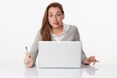 Écriture terrifiée de la femme 20s sur le PC sur le bureau blanc clairsemé Photo stock