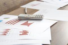 Écritures avec des données statistiques, des graphiques et des diagrammes se trouvant sur un OE photographie stock libre de droits