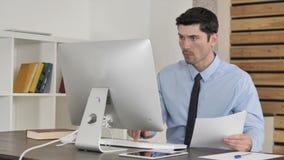 Écritures, jeune homme d'affaires Reading Documents et fonctionnement sur l'ordinateur banque de vidéos